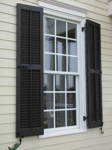 Exterior shutters with decorative iron hardware