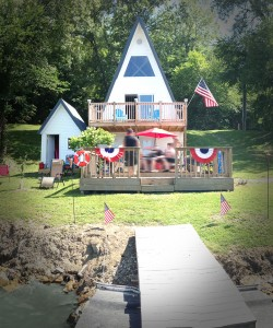 """The Tiny Lake House last year, after receiving a new roof, siding, and a cute """"mini-me"""" storage building."""